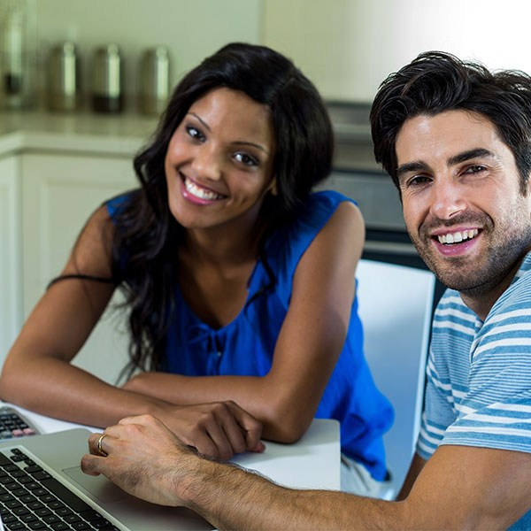 Couple looking at a computer smiling